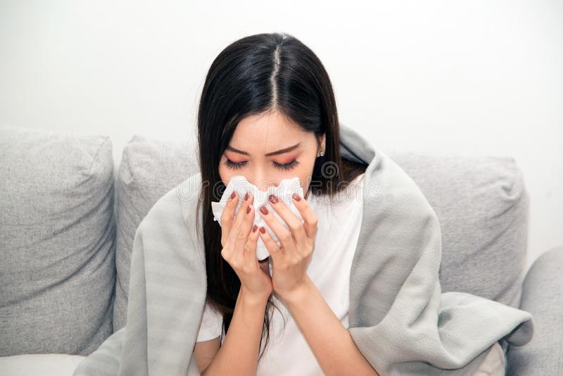 Asian women with stress that suffer from allergies and close the nose with tissue paper. Because of having sneezing all the time. stock images