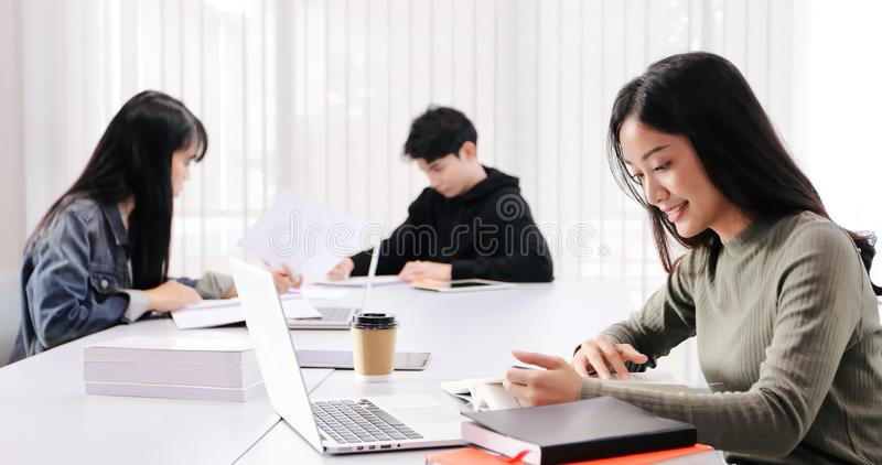 Asian women Students Smile and reading book and using notebook for helps to share ideas in the work and project. And also review stock photography