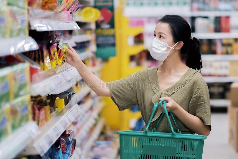 Asian women and surgical mask shopping some food in supermarket, covid-19 crisis. Asian woman and surgical mask shopping some food in supermarket, covid-19 royalty free stock images