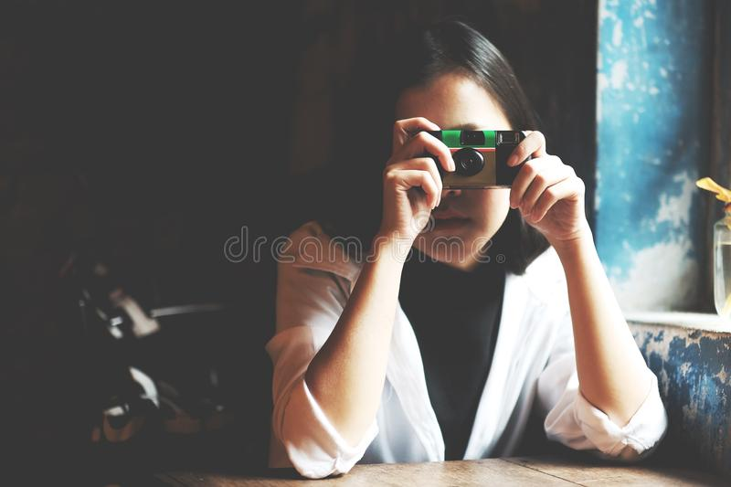 Asian women take a picture by film camera in coffee cafe, soft focus and low light picture stock photography