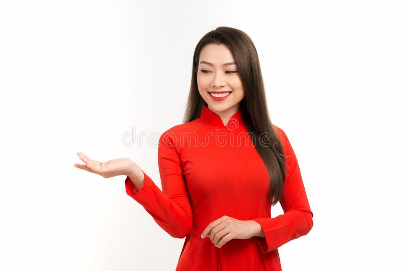 Asian women in traditional Vietnamese ao dai with a gesture of congratulations, isolated on a white background. Asian woman in traditional Vietnamese ao dai with royalty free stock image