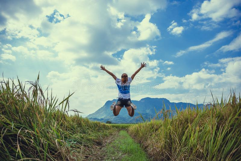 Asian women travel relax in the holiday. Stand natural touch mountain field. Jump stand glad middle field rice. Thailand stock photo