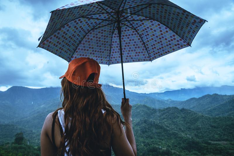 Asian women travel relax in the holiday. The women stood in rain umbrellas on the mountain. During the rainy season.Thailand. Asian woman travel relax in the royalty free stock image