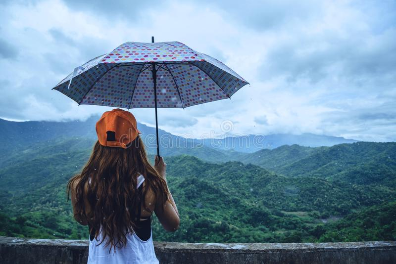 Asian women travel relax in the holiday. The women stood in rain umbrellas on the mountain. During the rainy season.Thailand. Asian woman travel relax in the stock images