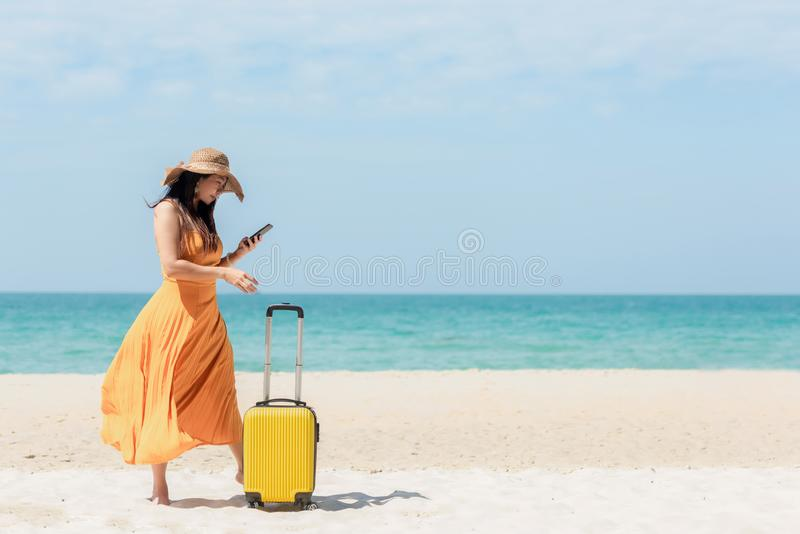 Asian women traveler holding yellow luggage walking and check in smart phone on the beach. Traveler and Tourism planning trips sum royalty free stock images