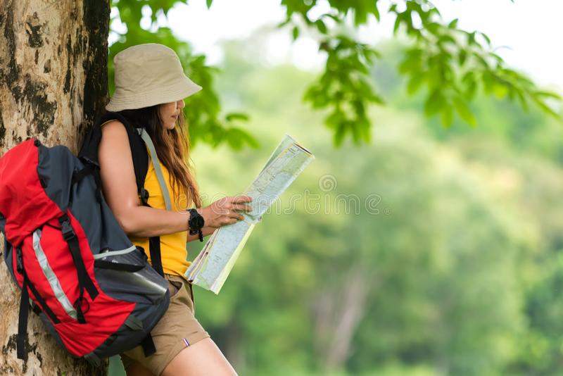 Asian women and traveler and tourism with backpack adventure holding map to find location directions and leisure destination stock photo