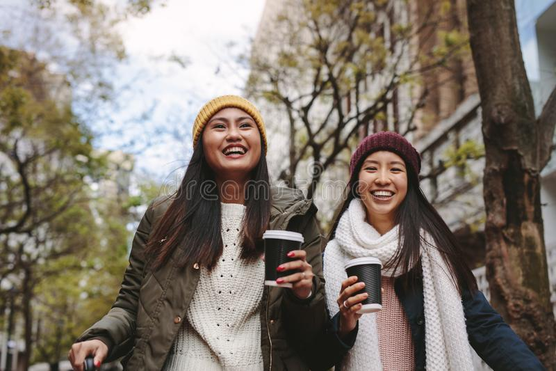 Asian women walking on street holding coffee stock photos