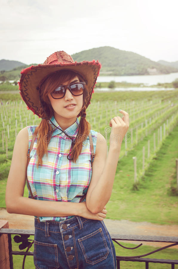 Asian women wear blue plaid shirt. Asian woman wear blue plaid shirt against green field royalty free stock images