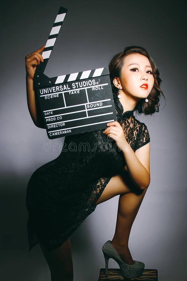 Asian women wear cheongsams and carry movie boards stock photography