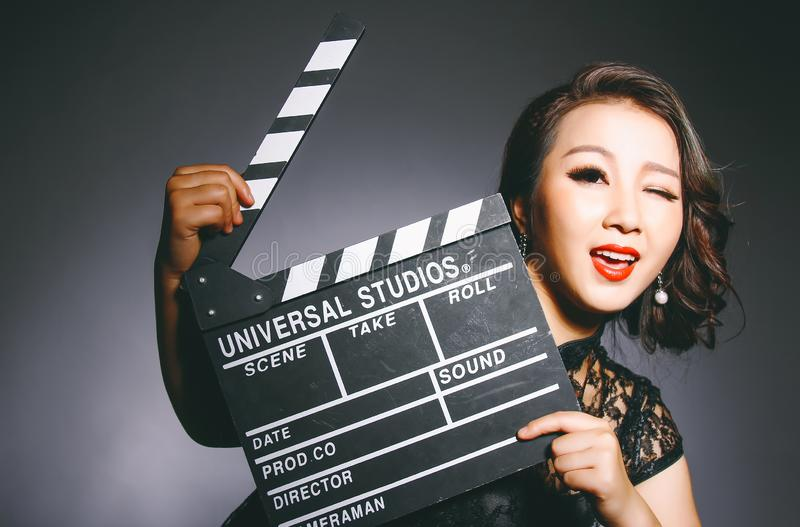 Asian women wear cheongsams and carry movie boards royalty free stock photos