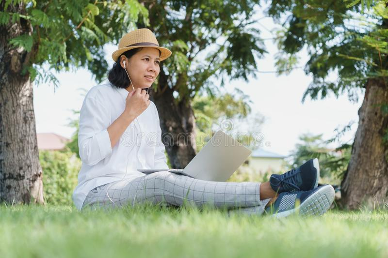 Asian women wear hat are using laptop with wired headphones while sitting on grass green  In the public park stock photography