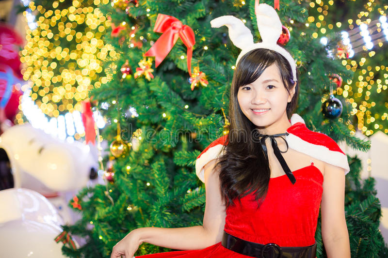 Asian women wearing santa claus clothes with tree royalty free stock images