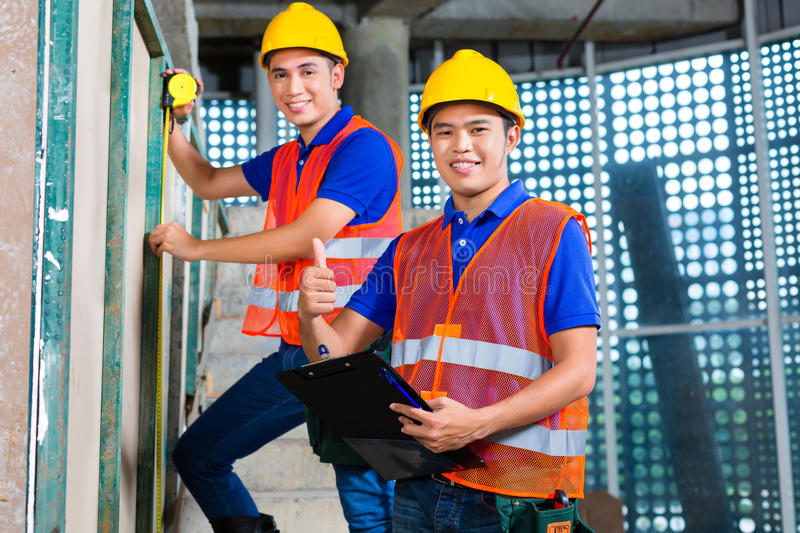 Asian worker controlling building on construction site stock photos