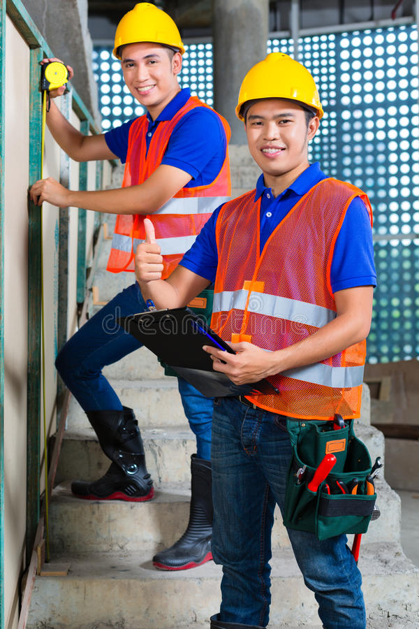 Asian worker controlling building on construction site royalty free stock images