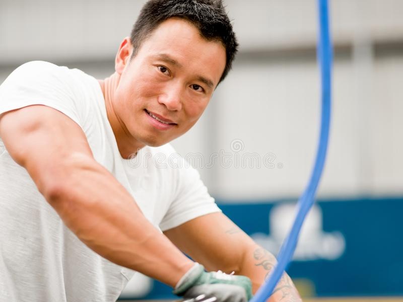 Asian worker in production plant on the factory floor. Portrait of asian worker in production plant working on the factory floor stock photo