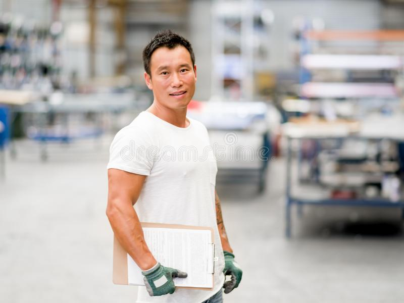 Asian worker in production plant on the factory floor. Portrait of asian worker in production plant working on the factory floor royalty free stock photos