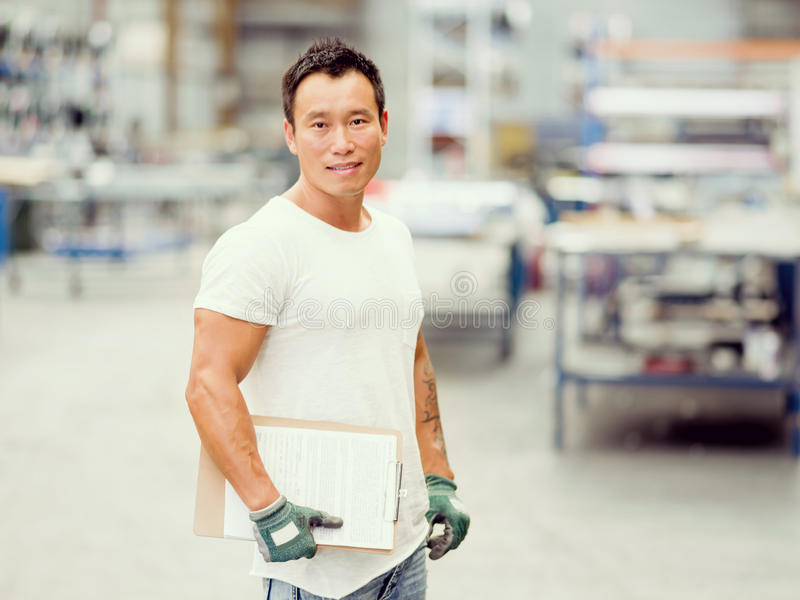 Asian worker in production plant on the factory floor. Portrait of asian worker in production plant working on the factory floor stock images