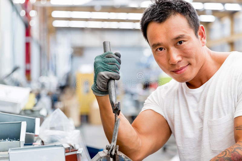 Asian worker in production plant on the factory floor. Portrait of asian worker in production plant working on the factory floor royalty free stock images