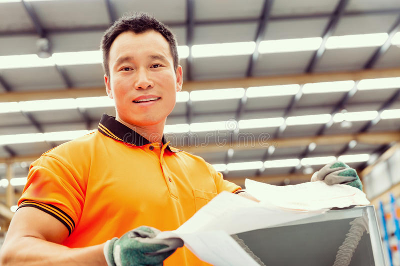 Asian worker in production plant on the factory floor. Portrait of asian worker in production plant working on the factory floor royalty free stock photography