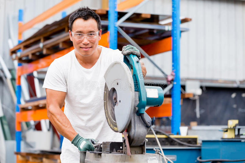 Asian worker in production plant on the factory floor. Portrait of asian worker in production plant working on the factory floor royalty free stock photo