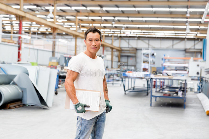 Asian worker in production plant on the factory floor. Portrait of asian worker in production plant working on the factory floor stock image