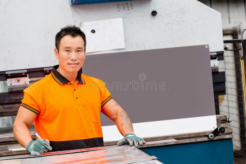 Asian worker in production plant on the factory. Portrait of asian worker in production plant working on the factory floor royalty free stock photography