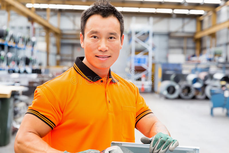 Asian worker in production plant on the factory. Portrait of asian worker in production plant working on the factory floor stock image