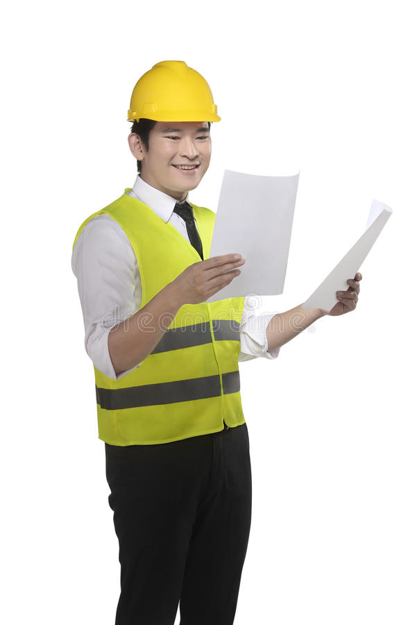 Asian worker wearing safety vest and yellow helmet holding blueprint. Isolated over white background royalty free stock photography