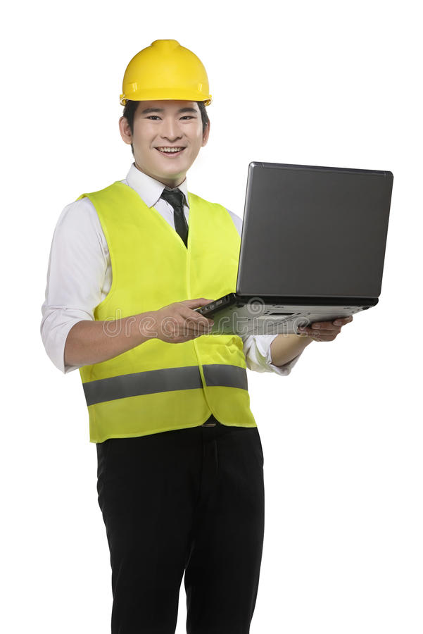 Asian worker wearing safety vest and yellow helmet. Holding laptop isolated over white background royalty free stock image
