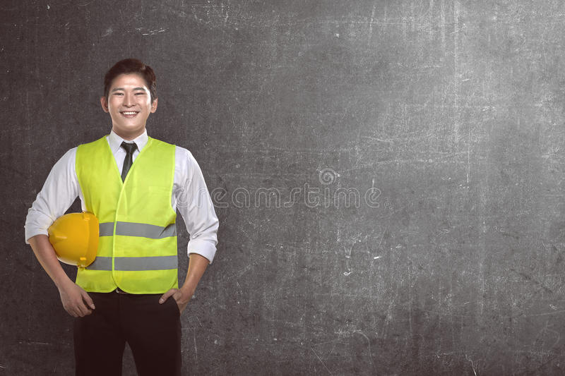 Asian worker wearing safety vest and yellow helmet. Over grunge background royalty free stock photo