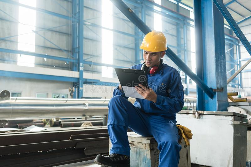 Asian worker writing observations about manufacturing stock photography