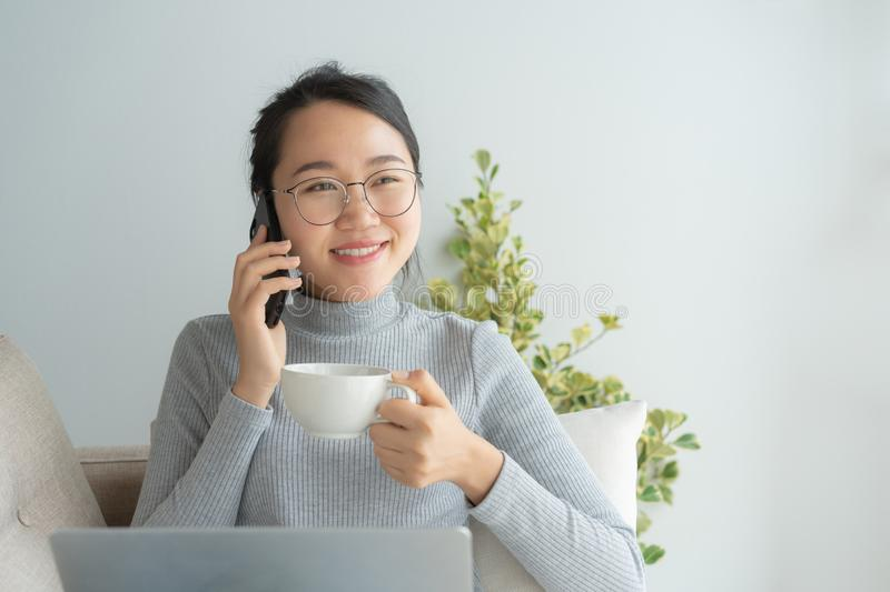 Asian working woman on her face wear glasses , smile , talk on telephone .Young business woman is drinking coffee and looking stock photos