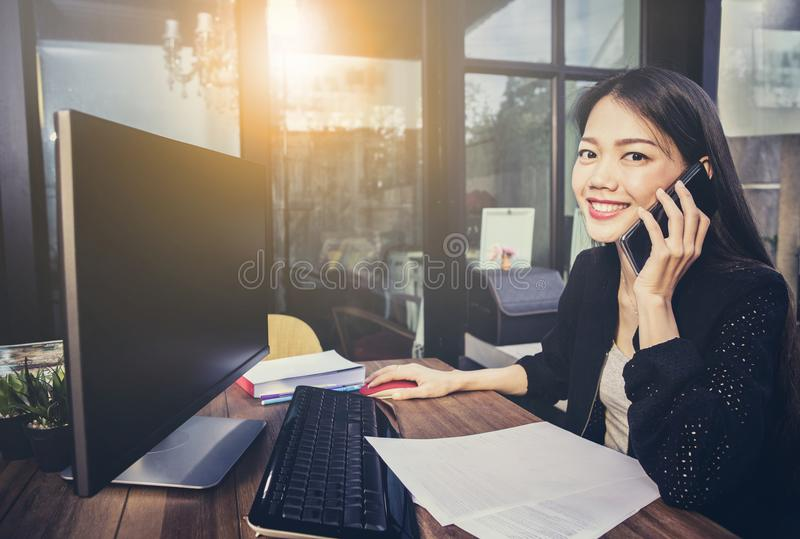 Asian working woman using computer in home office and talking o. N mobile phone with happiness face stock photos