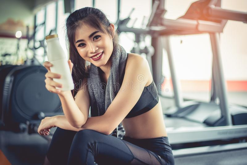 Asian workout woman showing milk bottle during break or relax. F. Ood drinks and Healthy concept. Fitness gym and equipment theme stock image