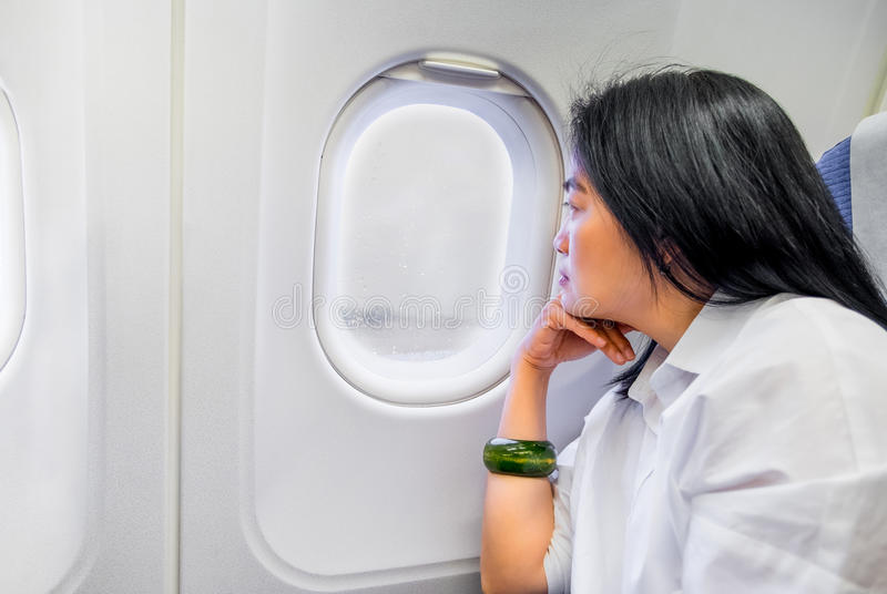 Asian wowan rest hand on chin in airplane cabin near window seat. With bad weather raining and feeling worry about dealy flight,transportation concept royalty free stock image