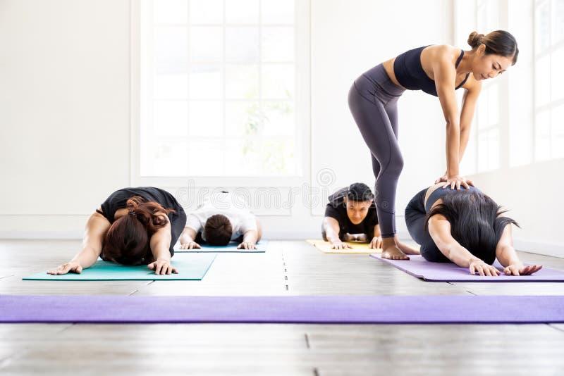 Asian Yoga coach tarining to yoga student stock image