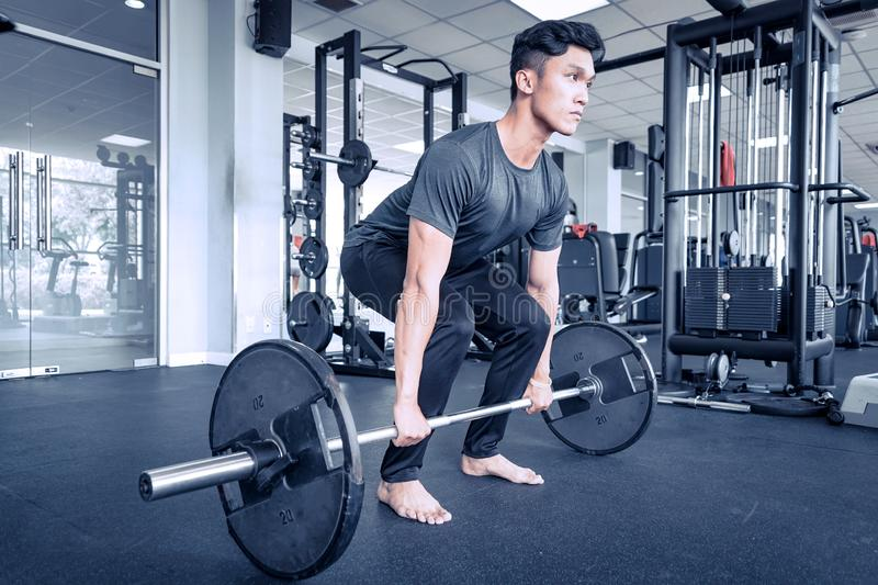 Asian young atheletic man in sportswear doing deadlift at gym with bare feet. Asian young atheletic man in sportswear doing deadlift at gym seriously with royalty free stock photos