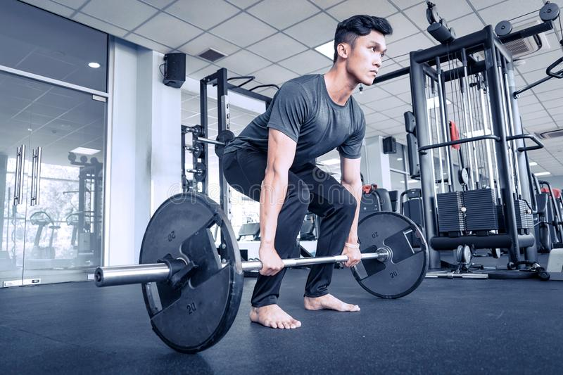 Asian young atheletic man in sportswear doing squat at gym with bare feet. Asian young atheletic man in sportswear doing heavy squat at gym seriously with stock image