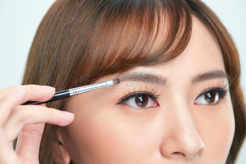 Asian young beautiful woman applying cosmetic powder brush on eyebrow, natural makeup, beauty face royalty free stock image