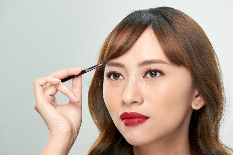 Asian young beautiful woman applying cosmetic powder brush on eyebrow, natural makeup, beauty face.  stock photography