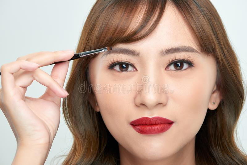 Asian young beautiful woman applying cosmetic powder brush on eyebrow, natural makeup, beauty face.  royalty free stock photography