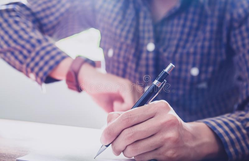 Asian young business man of student holding a pen writing letter on paper at home royalty free stock images