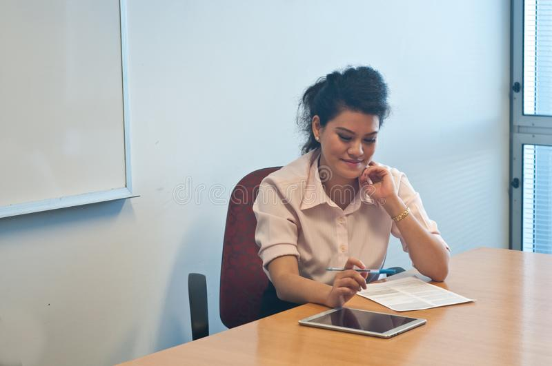 Business woman examining contract agreement in office. Asian young business woman is examining contract agreement in the office stock images