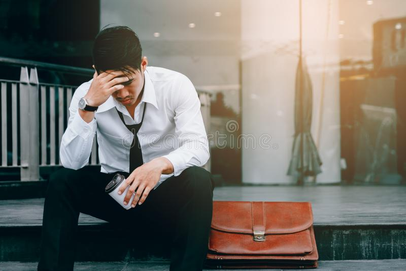 Asian young businessman stress sitting in front office with his. Hands covering his head against royalty free stock photography