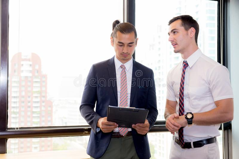 Asian young businessman two people holding clipboard and discussing work in the meeting room stock photos