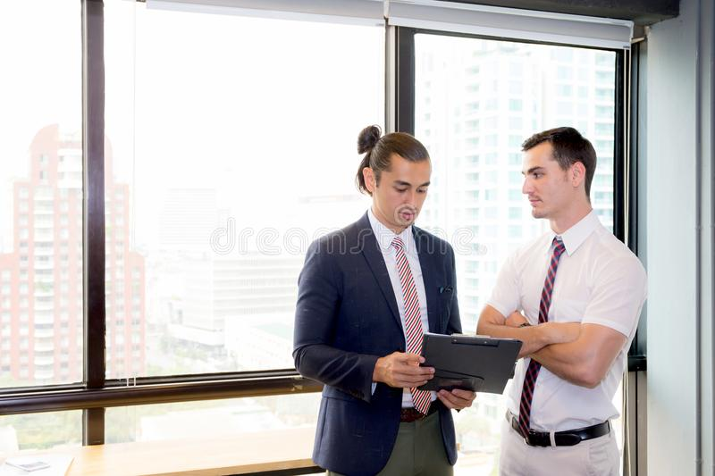 Asian young businessman two people holding clipboard and discussing work in the meeting room royalty free stock photos