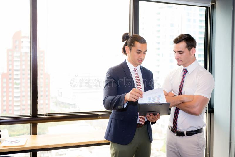 Asian young businessman two people holding clipboard and discussing work in the meeting room stock image