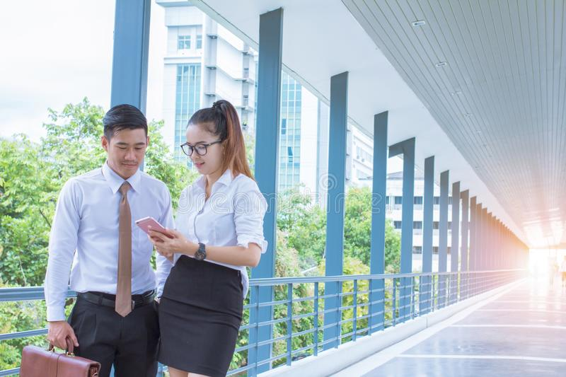 Asian young businessman ,woman holding mobile phone chat Meetings the commercial processes involved in promoting and selling and d royalty free stock photos