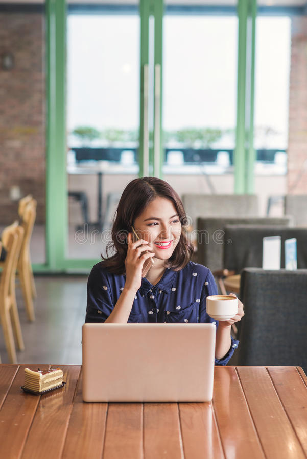 Asian young businesswoman in the cafe, on call and drinking coffee smiling royalty free stock photos