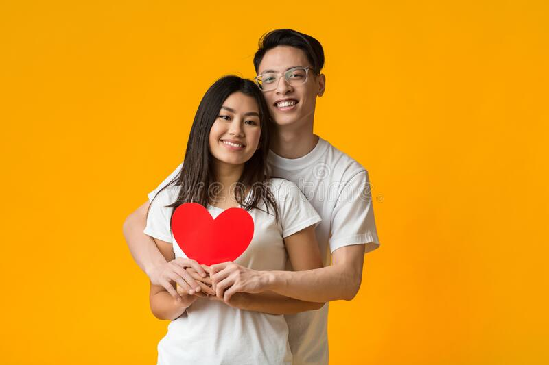 Asian couple hugging and holding big red heart stock photography